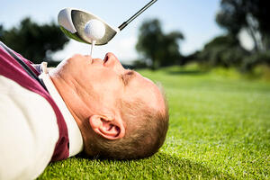 Golfer holding tee in his teeth on a sunny day at the golf course